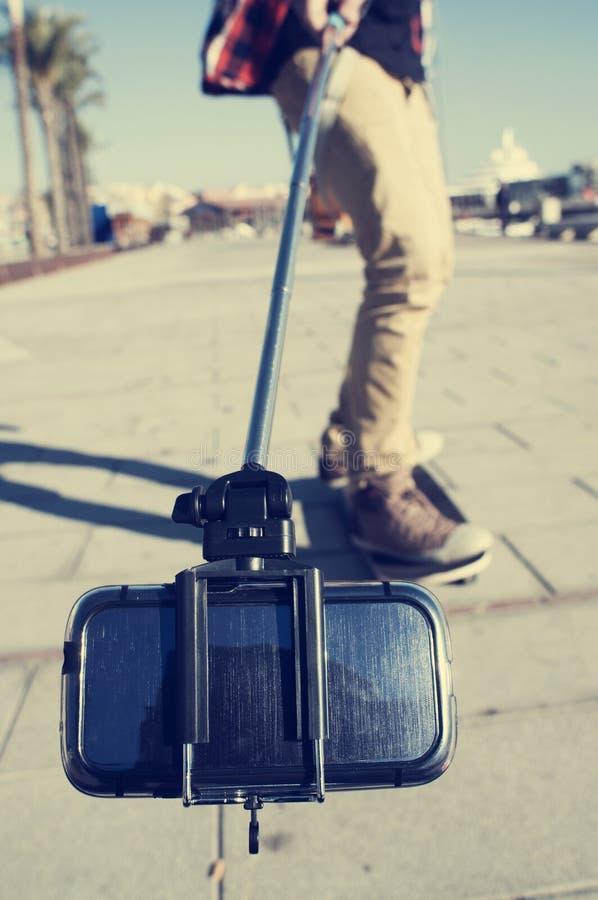 Schlittschuhläufer, der ein Selbstporträt oder ein Video mit einem selfie Stock nimmt stockfotografie