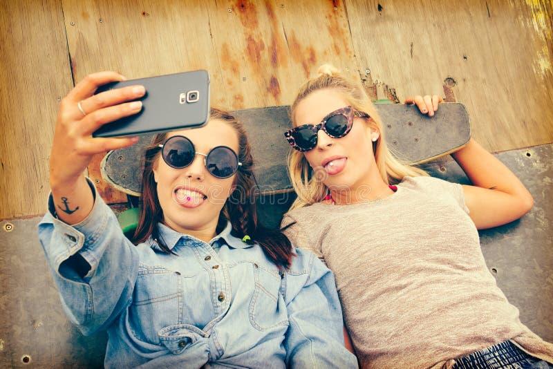 Schlittschuhläufer-Freundinnen, die Selfie nehmen stockbilder