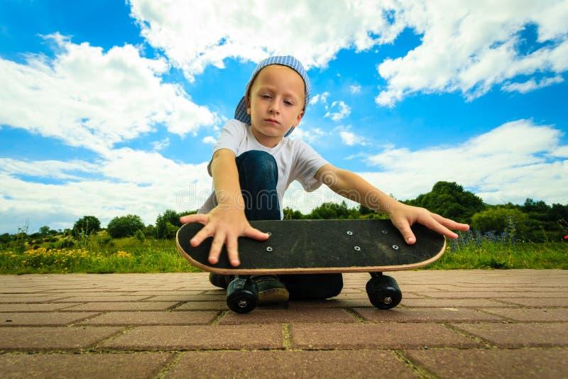 Schlittschuhläuferjungenkind mit seinem Skateboard Im Freienaktivität stockbild