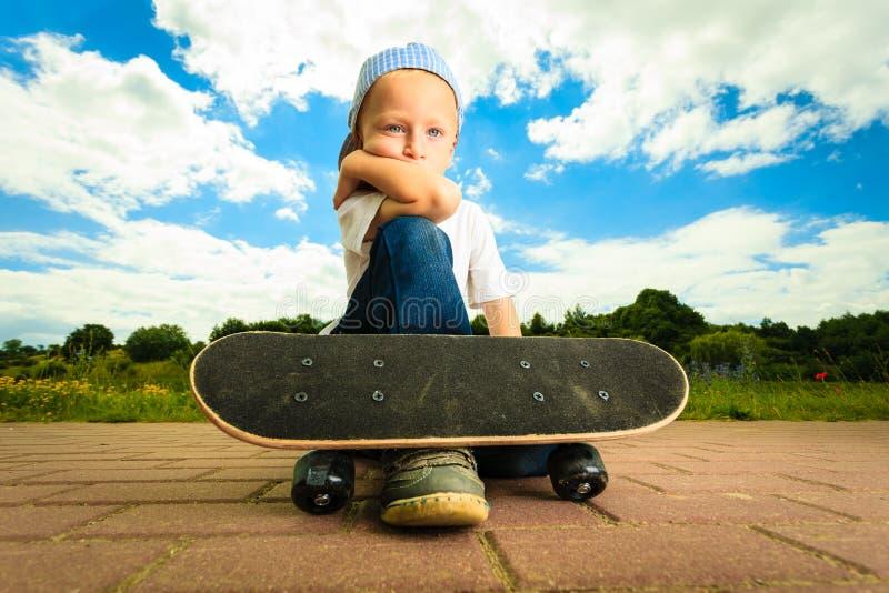 Schlittschuhläuferjungenkind mit seinem Skateboard Im Freienaktivität lizenzfreie stockfotografie