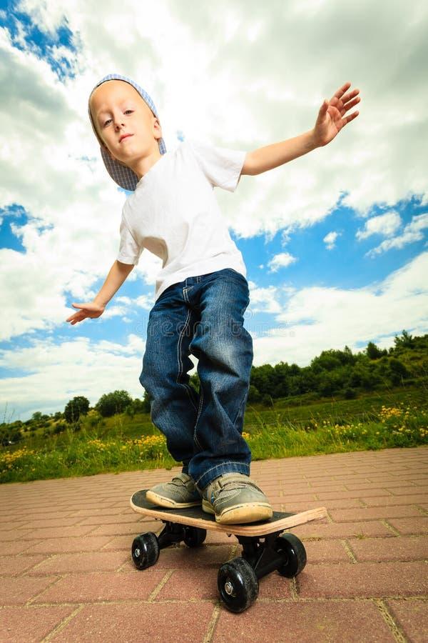 Schlittschuhläuferjungenkind mit seinem Skateboard Im Freienaktivität stockfotografie