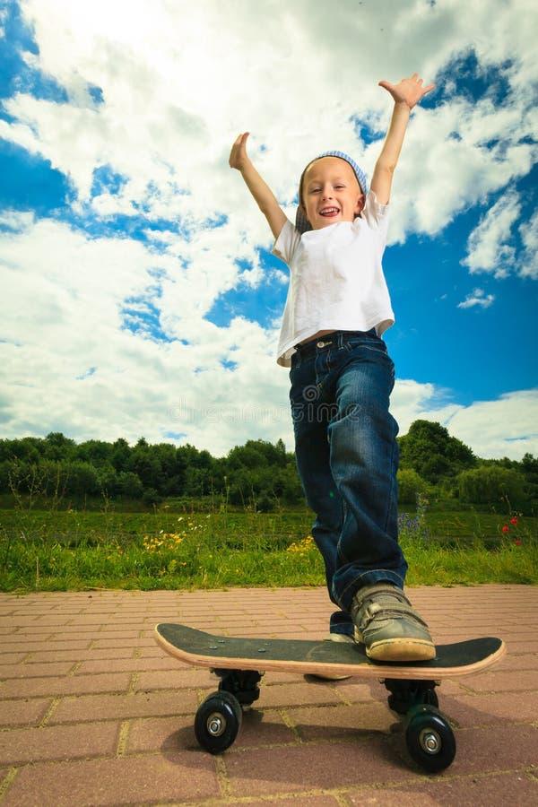 Schlittschuhläuferjungenkind mit seinem Skateboard Im Freienaktivität stockfoto