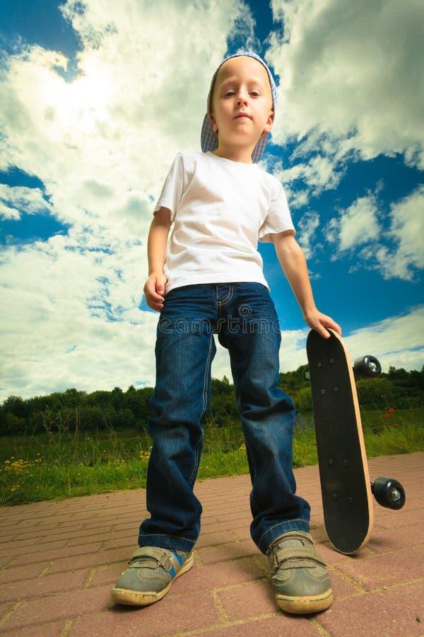 Schlittschuhläuferjungenkind mit seinem Skateboard Im Freienaktivität stockbilder