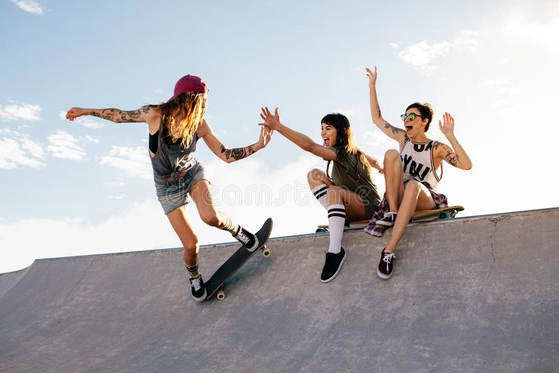 Schlittschuhläufermädchen-Reitskateboard am Rochenpark mit Freunden stockbild