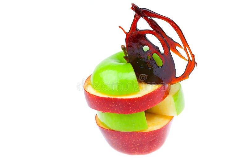 Schlitzen Sie die Apfelscheiben und -karamel auf, die auf Weiß getrennt werden lizenzfreie stockfotos