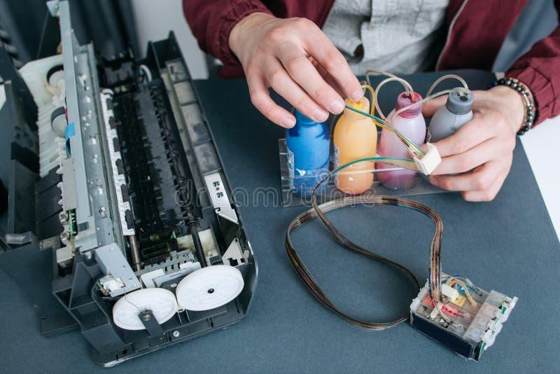 Schlosser, der CISS in der Draufsicht des Bürodruckers repariert stockfotos