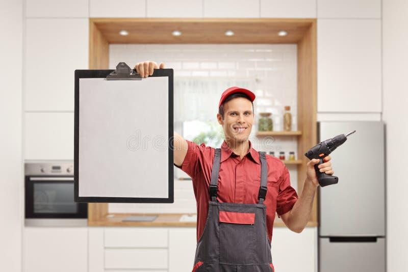 Schlosser, der eine Bohrgerätmaschine hält und ein leeres Klemmbrett zeigt lizenzfreies stockbild