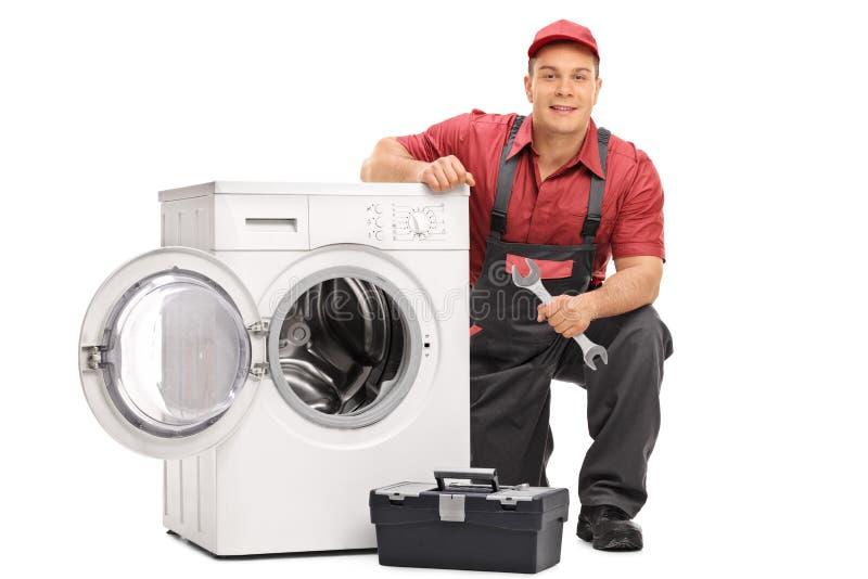 Schlosser, der eine Waschmaschine repariert stockfotos