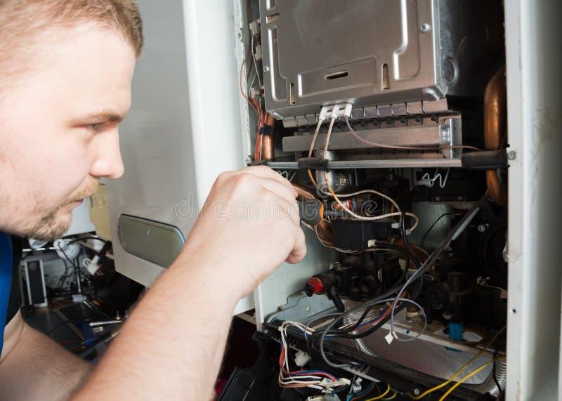 Schlosser, der einen GasWarmwasserbereiter mit einem Schraubenzieher repariert stockfoto