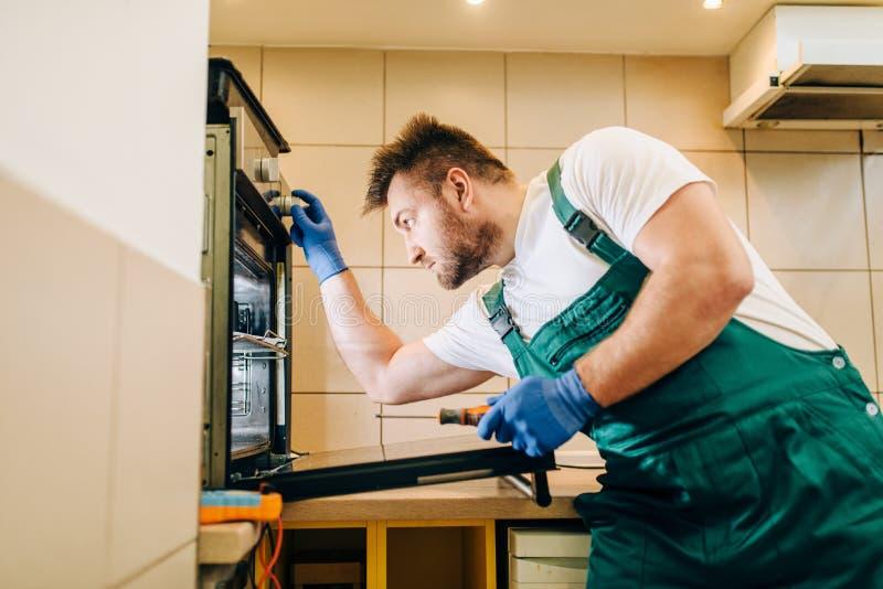 Schlosser in der Uniform überprüft den Ofen, Techniker stockfotos