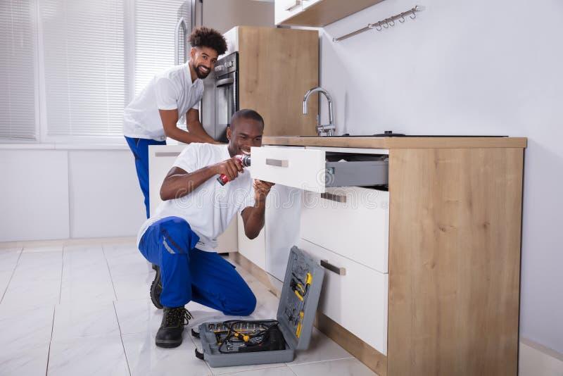 Schlosser, die das hölzerne Kabinett in der Küche reparieren stockbilder