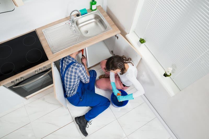 Schlosser-Fixing Pipe While-Frau, die nassen Stoff zusammendrückt stockfoto