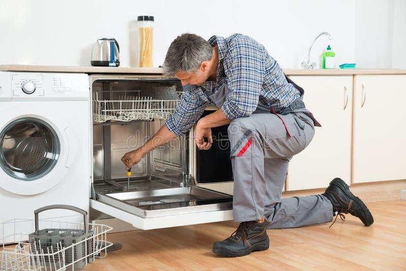 Schlosser-Repairing Dishwasher With-Schraubenzieher in der Küche stockbild