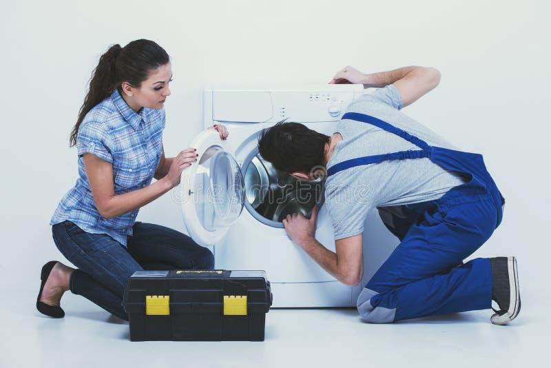 Schlosser repariert eine Waschmaschine für Hausfrau Weißer Hintergrund stockbild