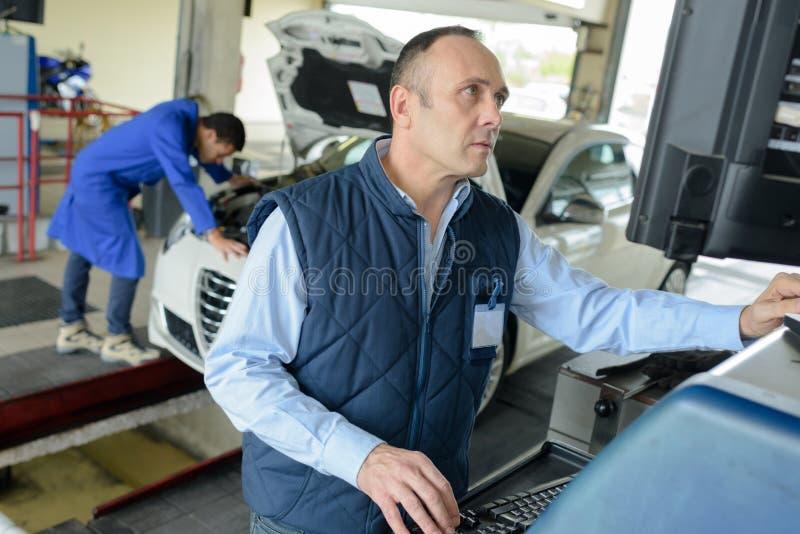 Schlosserautomechaniker in der Garage lizenzfreie stockfotos
