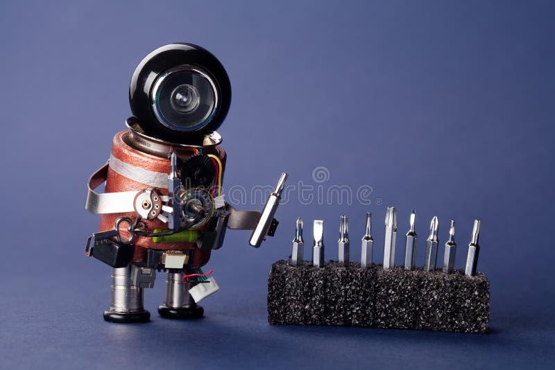Schlosserroboter mit Schraubenziehersatz Spaßspielzeugcharakter, schwarzer Sturzhelmkopf und Heimwerkerinstrument Makroansicht, f stockbild