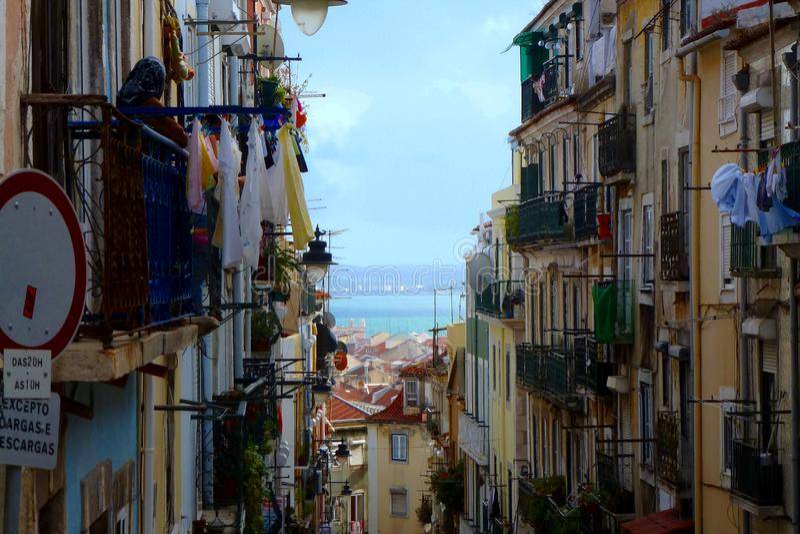 Schmale Gasse Lissabons mit alten Wohngebäuden und trocknen Stoffen stockbilder