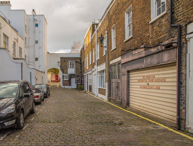 Schmale Gasse mit typischen englischen Gebäuden auf der rechten Seite stockbilder