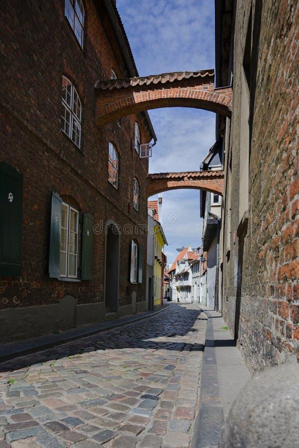Schmale Kopfsteinstra?e mit B?gen zwischen den historischen H?usern in der alten Stadt von Luebeck, ber?hmter touristischer Besti lizenzfreies stockbild