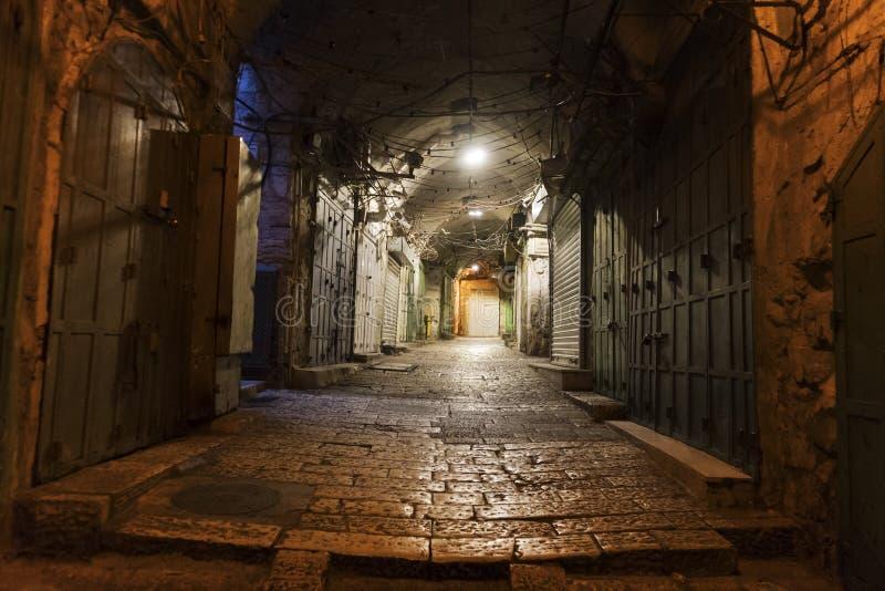 Schmale Pflasterstraße in der alten mittelalterlichen Stadt mit belichteten Häusern und Pflasterung Nachtaufnahme des Seitendurch stockfotografie