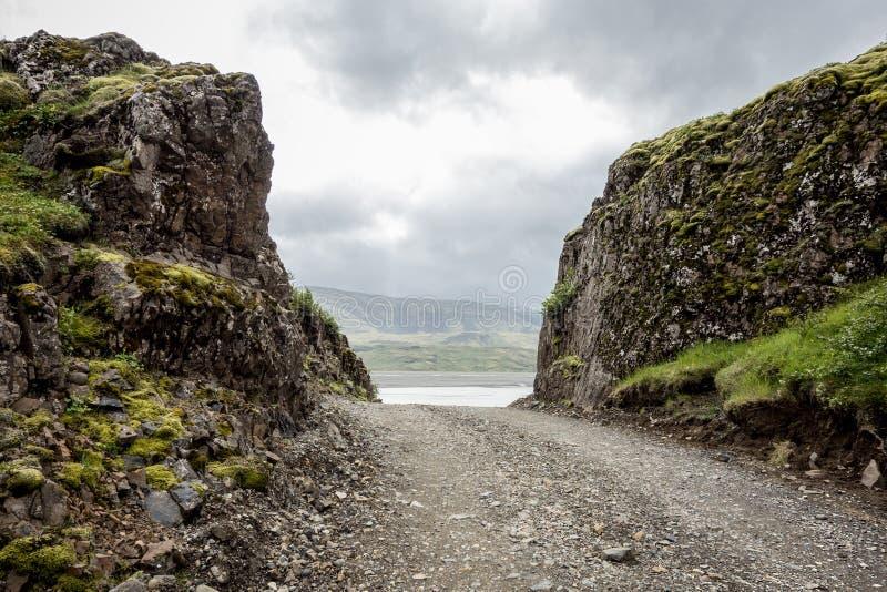 Schmale Schotterstraße zwischen zwei Felsen in Island lizenzfreie stockfotografie