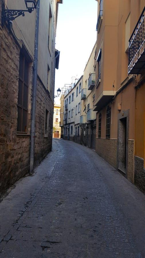 Schmale spanische Straße mit den Stein- und gemalten Wänden stockfoto