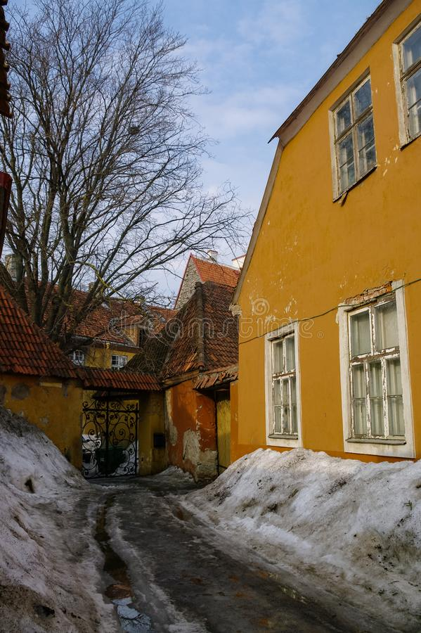Schmale Straße in der Altstadt von Tallinn mit Schneebänken Estland stockbilder