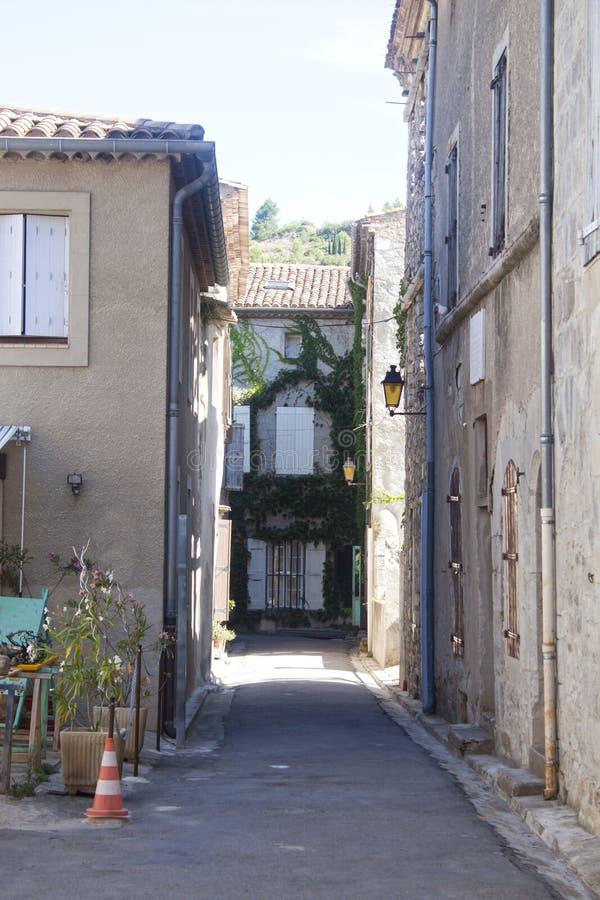 Schmale Straße mit Häusern mit Efeu in Lagrasse stockbild