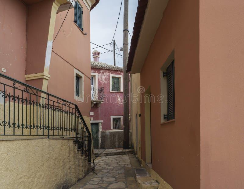 Schmale Straße und mit alten roten Häusern mit abblätternder Fassade, grüner Tür und Fenster, Weinleseblick, Korfu Griechenland stockfotografie
