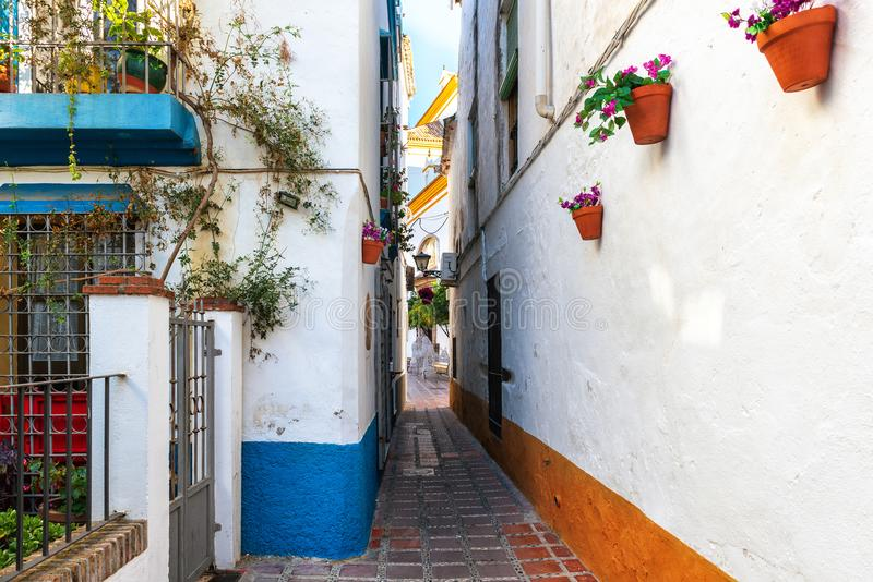 Schmale Straße von Marbella-Stadt mit den weißen Wänden verziert mit Blumentöpfen lizenzfreie stockfotos
