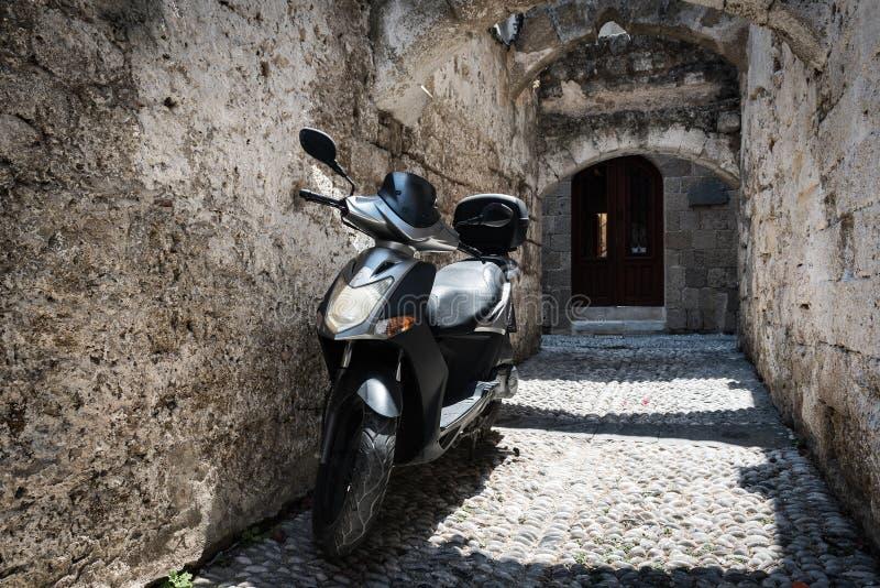 Schmale Straße von Rhodos-Stadt mit Bewegungsroller parkte nahe Steinwand lizenzfreie stockbilder