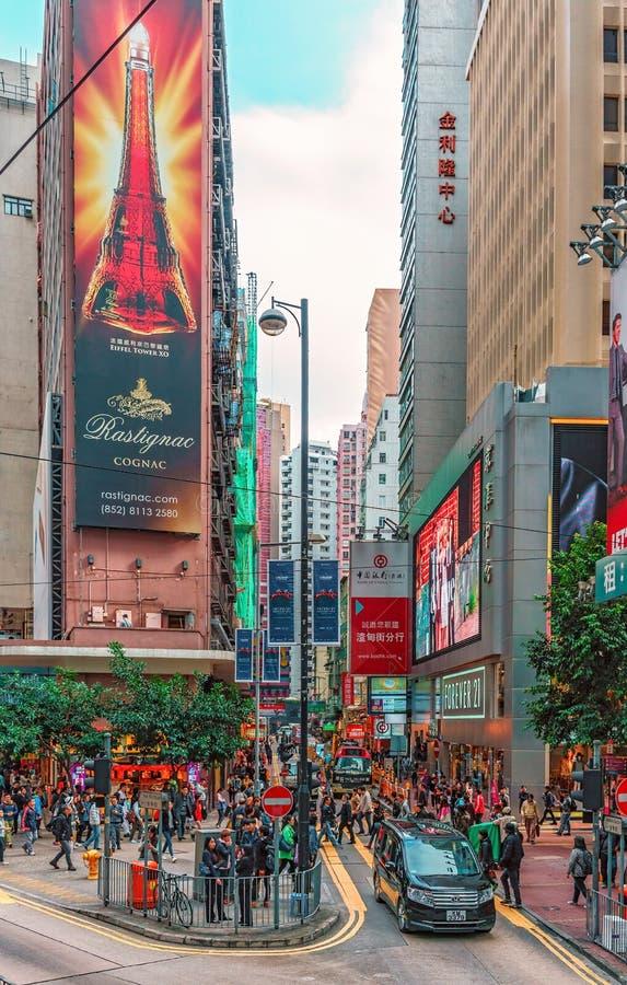 Schmale Straßen von Hong Kong werden mit Leuten gedrängt Stadtbild mit Wolkenkratzern Vertikale Ansicht stockfotografie