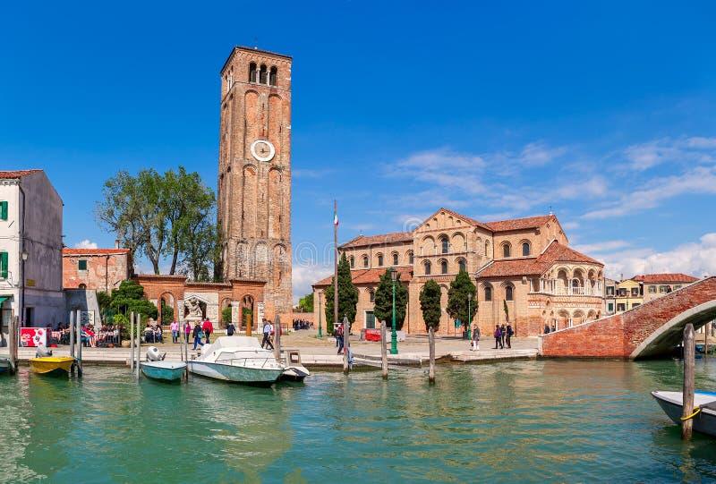 Schmaler Kanal, Kirche und hoher Glockenturm mit Uhr in Murano lizenzfreies stockbild