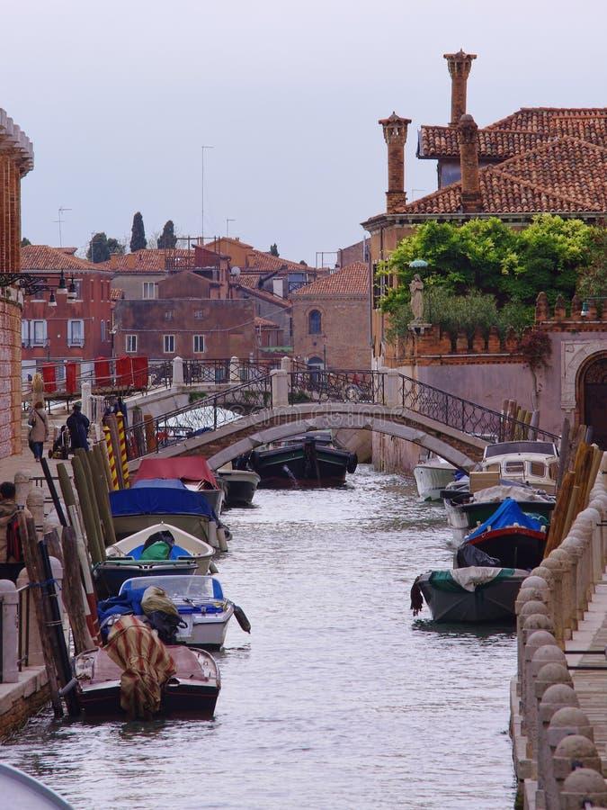 Schmaler Kanal mit Booten in Venedig-Stadt stockfotos