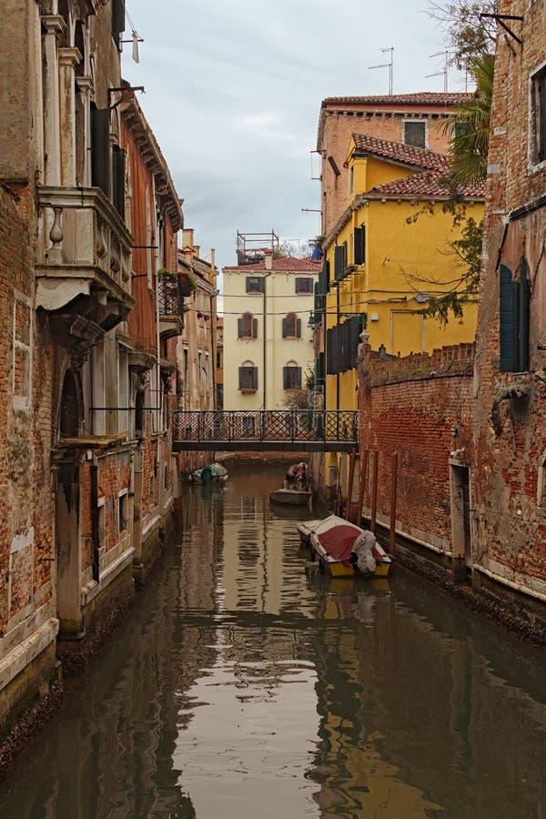Schmaler Kanal mit festgemachten Booten zwischen Wohngebäuden im nicht-touristischen Teil von Venedig, Italien Stadtbild am regne lizenzfreie stockfotografie