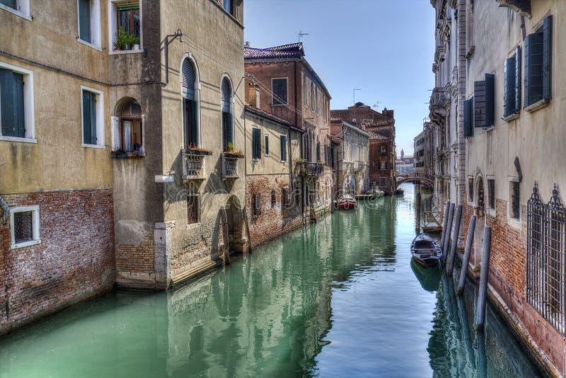 Schmaler Kanal mit kleinen Booten in Venedig, Italien stockfotografie