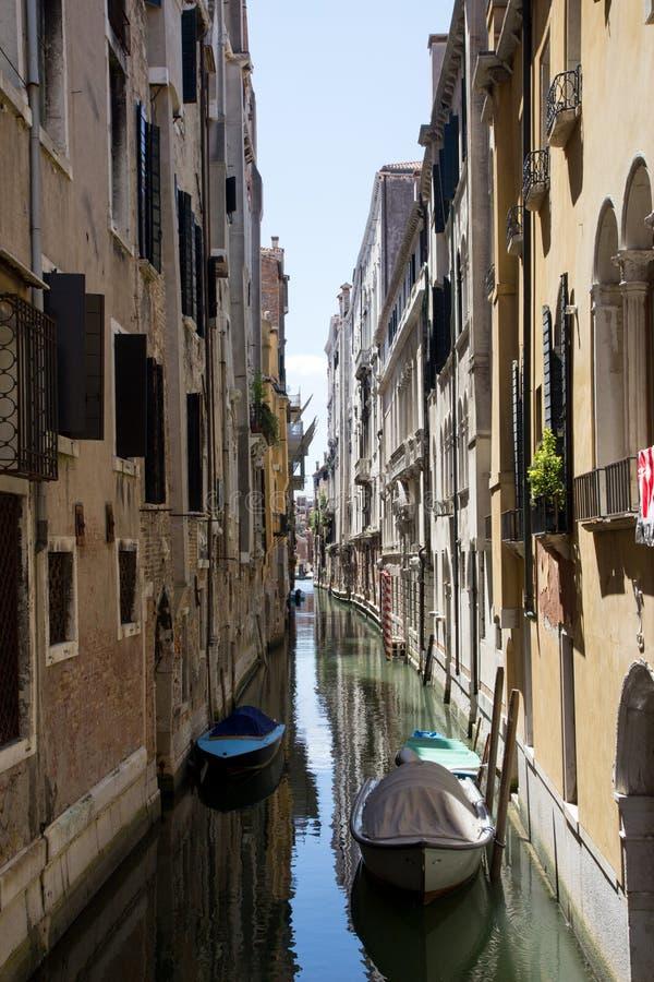 Schmaler Kanal in Venedig mit Booten lizenzfreie stockfotos