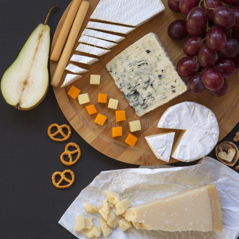 Schmecken von verschiedenen Arten von Käsen mit Früchten, Brezeln, Walnüssen und Brotstöcken auf dunklem Hintergrund Lebensmittel lizenzfreies stockfoto