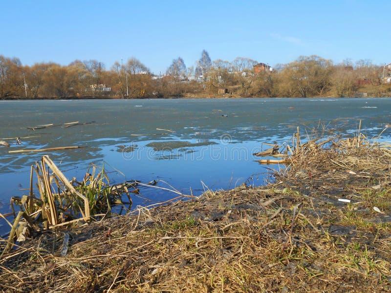 Schmelzendes Eis auf dem ländlichen Teich im Frühjahr stockfotos