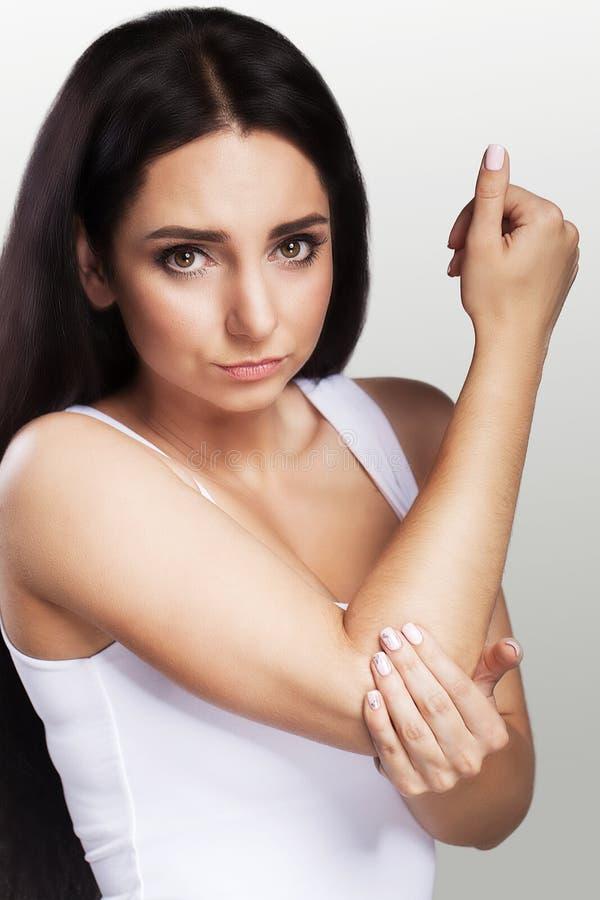 Schmerz im Winkelstück Das Mädchen hält ihre Hand für einen Ellbogen Schmerzliche Empfindungen im Bereich der Hand versetzung bru lizenzfreie stockfotos