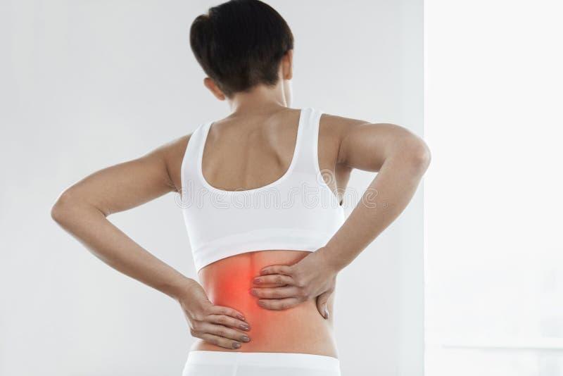 schmerz Schöne Frau, die schmerzliche Gefühls-herein Rückseite, Rückenschmerzen hat lizenzfreie stockfotografie