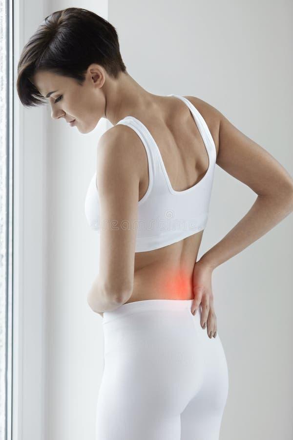 schmerz Schöne Frau, die schmerzliche Gefühls-herein Rückseite, Rückenschmerzen hat stockbilder