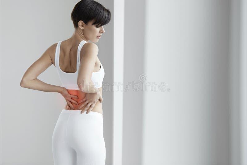 schmerz Schöne Frau, die schmerzliche Gefühls-herein Rückseite, Rückenschmerzen hat lizenzfreie stockbilder