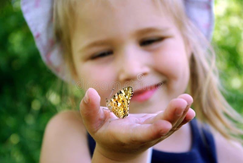 Schmetterling, der auf der Hand eines Kindes sitzt Kind mit einem Schmetterling Schmetterlingsdistelfalter auf der Hand eines kle stockfotos