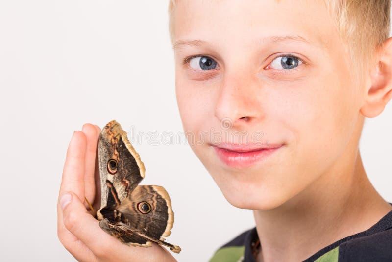 Schmetterling Saturnia auf Kinderhand lizenzfreie stockfotografie