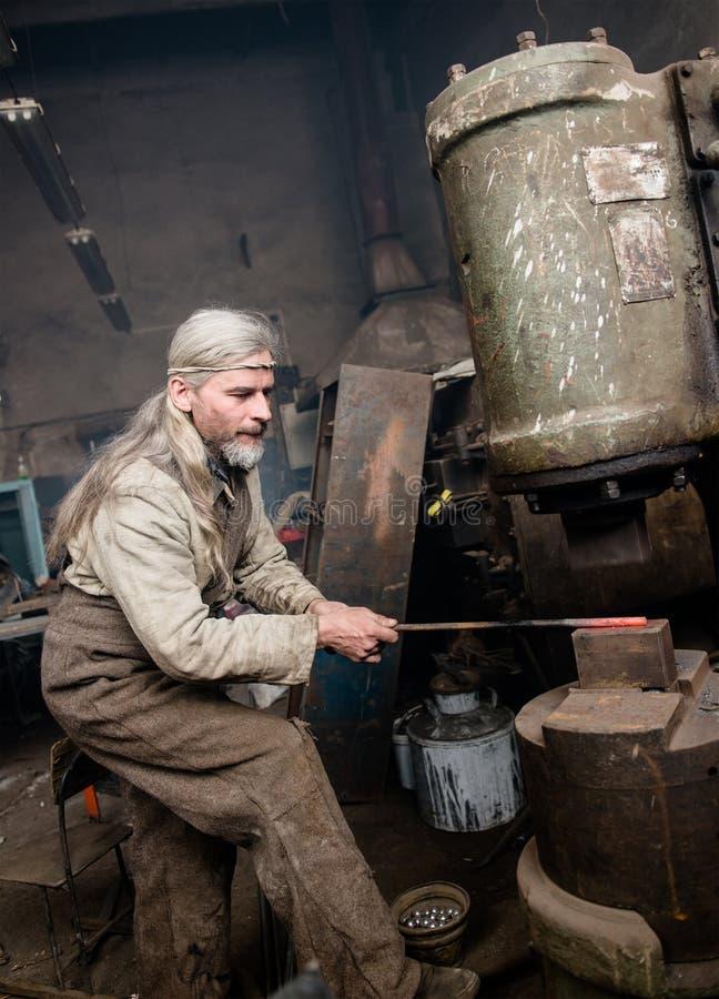 Schmied arbeitet mit einem Energiehammer lizenzfreie stockbilder
