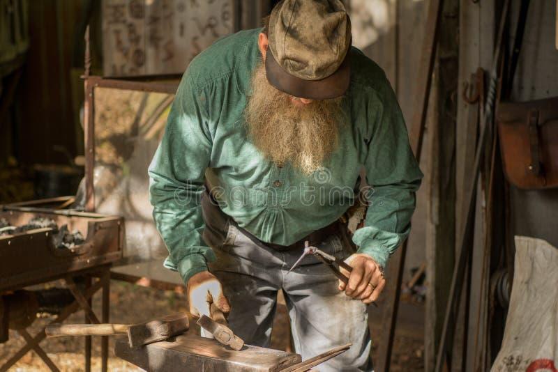 Schmied, der mit seinem Hammer und Ambosse arbeitet stockbilder