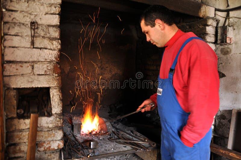 Schmied schmiedet ein glühendes Eisen in der Schmiede stockbilder