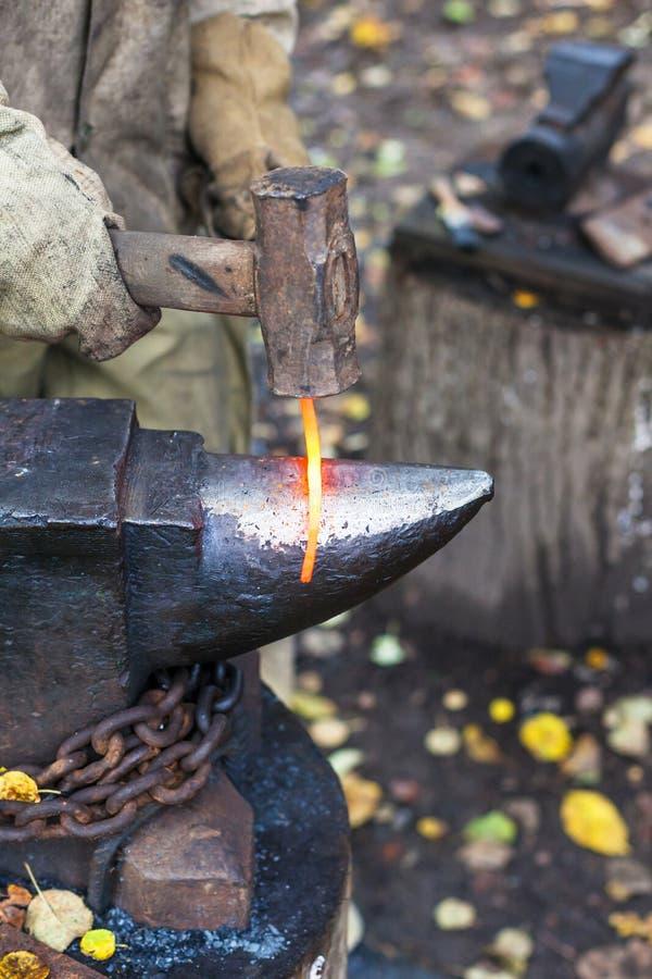 Schmied schmiedet rote glühende Eisenstange auf Ambosse lizenzfreies stockfoto