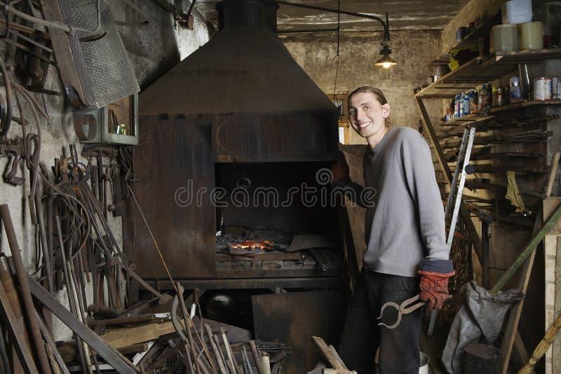 Schmied Standing By Forge in der Werkstatt lizenzfreie stockfotos